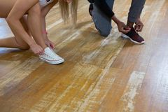 Low section of dancers tying shoelaces on floor Royalty Free Stock Photo