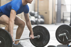 Low section of dedicated man lifting barbell in crossfit gym. Low section of dedicated men lifting barbell in crossfit gym Royalty Free Stock Photography