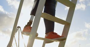 Low section of disabled woman climbing ladder in the park 4k. Low section of disabled woman climbing ladder in the park. Sun shining in the background 4k stock video footage