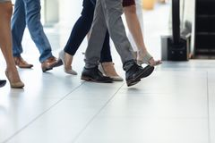 Diverse executives walking in the same direction in hall. Low section of diverse executives walking in the same direction in hall royalty free stock images