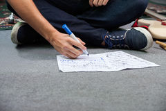 Low Section Of Drummer Writing Notes While Sitting On Floor Stock Photo