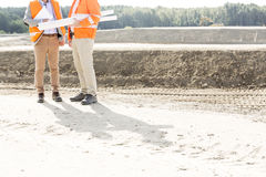 Low section of engineers with blueprints standing at construction site Royalty Free Stock Photography