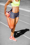 Low section of female athlete stretching leg on sports track stock image