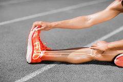 Low section of female athlete stretching on sports track royalty free stock photo