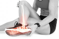 Low section of female athlete suffering from ankle pain on white background Stock Images