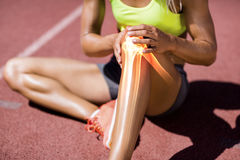 Low section of female athlete suffering from knee pain. While sitting on track during sunny day royalty free stock images