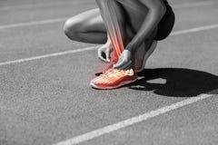 Low section of female athlete tying shoelace on track Stock Photo