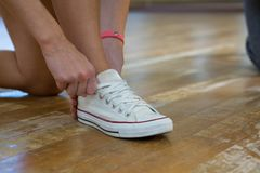 Low section of female dancer tying shoelace Royalty Free Stock Photo