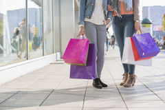 Low section of female friends holding shopping bags on sidewalk Royalty Free Stock Photography