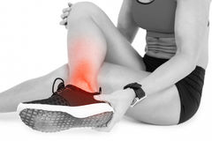 Low section of female sportsperson suffering from ankle pain on white background Royalty Free Stock Photo