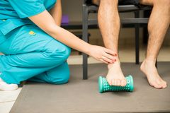 Therapist Assisting Patient To Use Foot Roller For Plantar Fasciitis stock photography