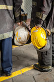 Low Section Of Firemen Holding Helmets Stock Images