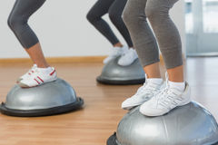 Low section of fit people performing step aerobics exercise Stock Images