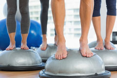 Low section of fit people standing on exercise equipment Royalty Free Stock Photos
