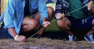 Low section of friends nailing tent peg 4k. Low section of friends nailing tent peg in parkland 4k stock video