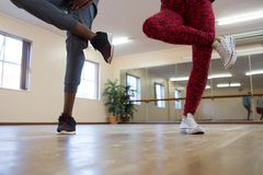 Low section of friends rehearsing dance on hardwood floor Royalty Free Stock Images