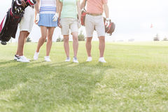 Low section of friends standing at golf course Stock Photography