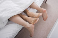 Low section of intimate couple in bed Stock Images