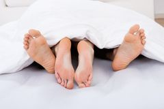 Low section of intimate couple under blanket Royalty Free Stock Photo