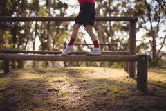 Low section of kid walking on obstacle during obstacle course royalty free stock photo