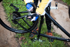 Low section of male biker repairing mountain bike Royalty Free Stock Photo