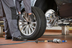 Low section of male mechanic repairing car's tire in repair shop Royalty Free Stock Images