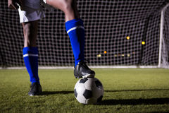 Low section of male soccer player standing with ball on field. Low section of male soccer player standing with ball against goal post on playing field Royalty Free Stock Photography