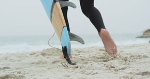 Low section of male surfer walking with surfboard on the beach 4k