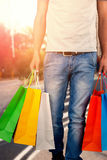 Composite image of low section of man carrying colorful shopping bag against white background Stock Image
