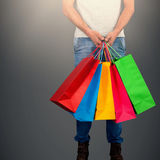 Composite image of low section of man carrying colorful shopping bag standing against white backgrou Royalty Free Stock Images