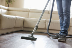 Low section of man cleaning hardwood floor with vacuum cleaner Stock Image