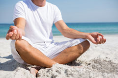 Low section of man doing meditation at beach. Low section of man doing meditation while sitting at beach Royalty Free Stock Images