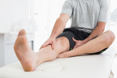 Low section of a man with hands on a painful leg Stock Photo