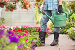 Low section of man holding watering can at greenhouse Stock Photography