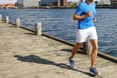 Low Section Of Man Jogging On Boardwalk By River Stock Images