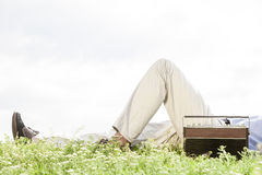 Low section of man lying by vintage radio on grass against clear sky Stock Images