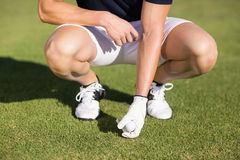 Low section of man placing golf ball on tee Royalty Free Stock Photos