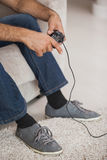 Low section of a man playing video games in living room. Close-up low section of a man playing video games in the living room at home Royalty Free Stock Image