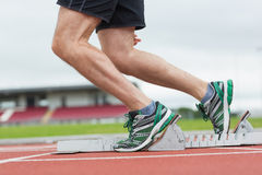 Low section of a man ready to race on running track Royalty Free Stock Images