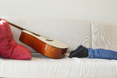 Low section of man's leg with guitar kept on sofa Stock Photography