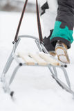 Low section of man with sled walking in snow Stock Images