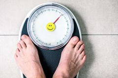 Low section of man standing on weight scale stock image