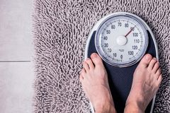Low section of man standing on weight scale stock photos