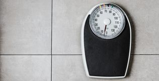 Low section of man standing on weight scale royalty free stock image