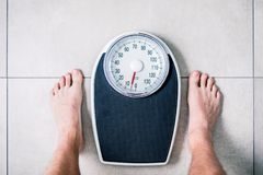 Low section of man standing on weight scale stock photography