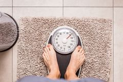 Low section of man standing on weight scale royalty free stock images