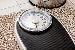 Low section of man standing on weight scale royalty free stock photos