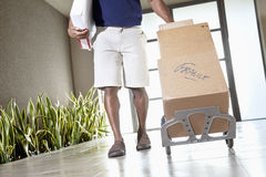 Low section of a man walking with packages on handtruck Stock Photo