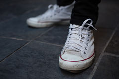 Low section of man wearing white canvas shoes Stock Photo