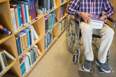 Low section of a man in wheelchair in the library Stock Image